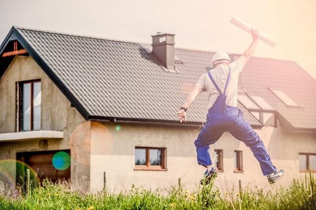 homem comemorando construção de casa